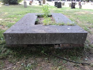 """Grave in Kingston cemetery in Portsmouth.From location in cemetery believed to be the grave of Robert George Titheradge and family who were buried in a""""brick grave"""" No visible writing on the derelict grave"""